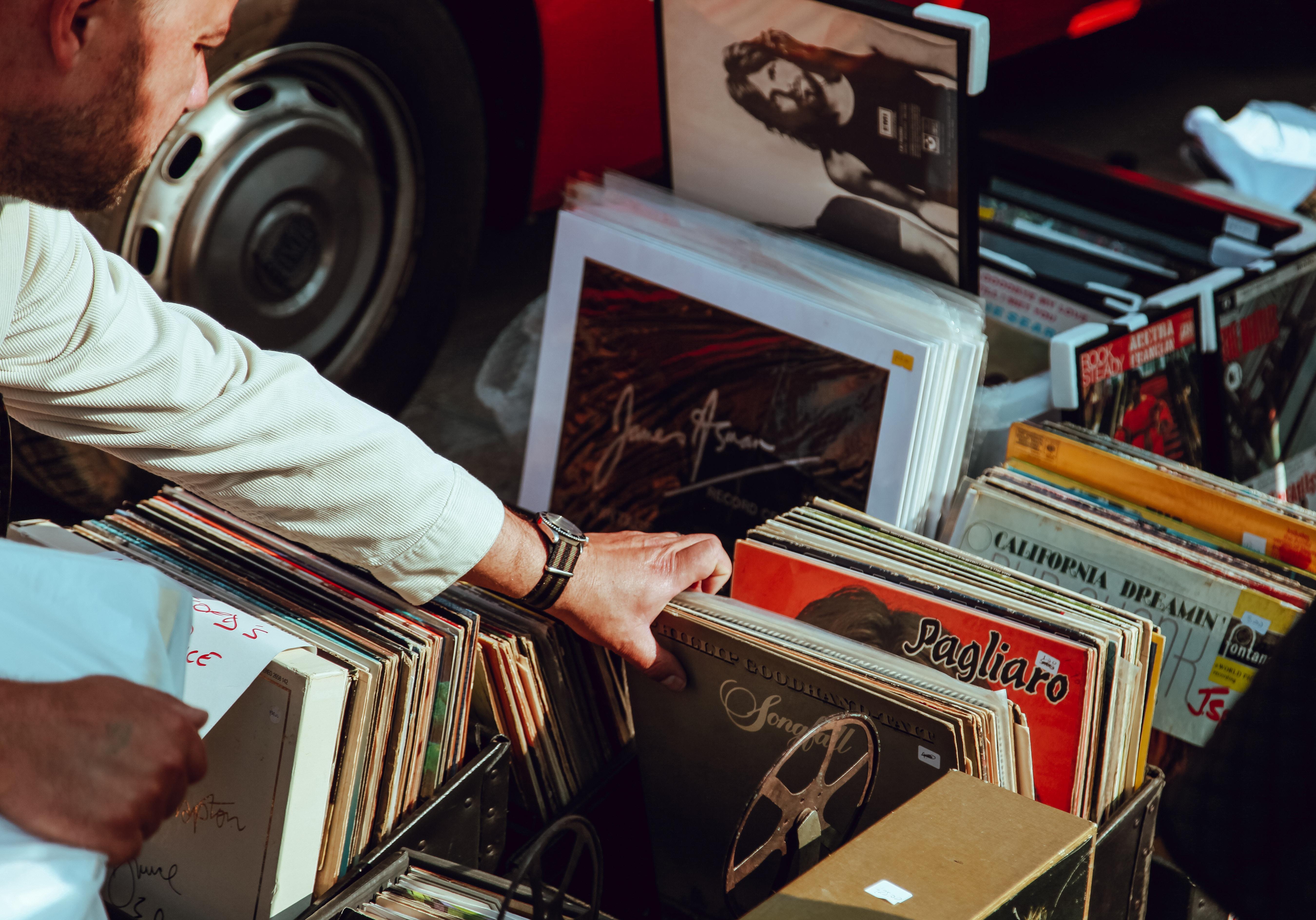 man digging through crate of vinyl