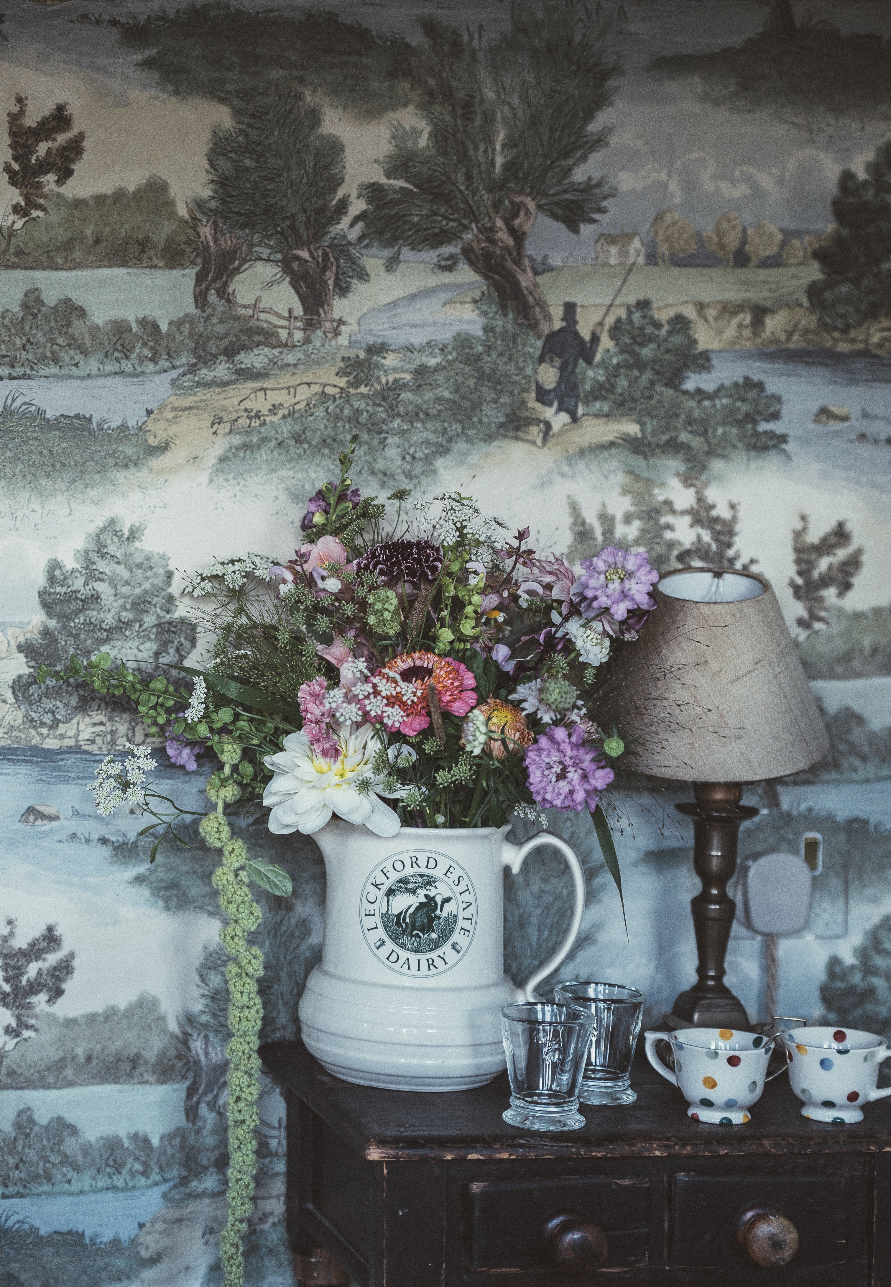vase of flowers in front of vintage wallpaper